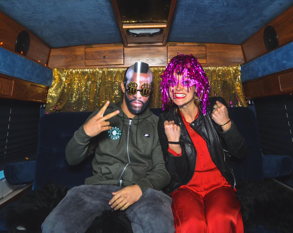 Zwei verkleidete Personen sitzen in einem samtblauen Fotobus und machen ein Selfie.