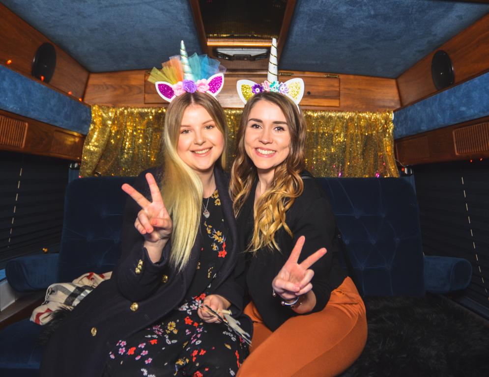Zwei Mädchen sitzen verkleidet in einem samtblauen Fotobus und machen ein Selfie.