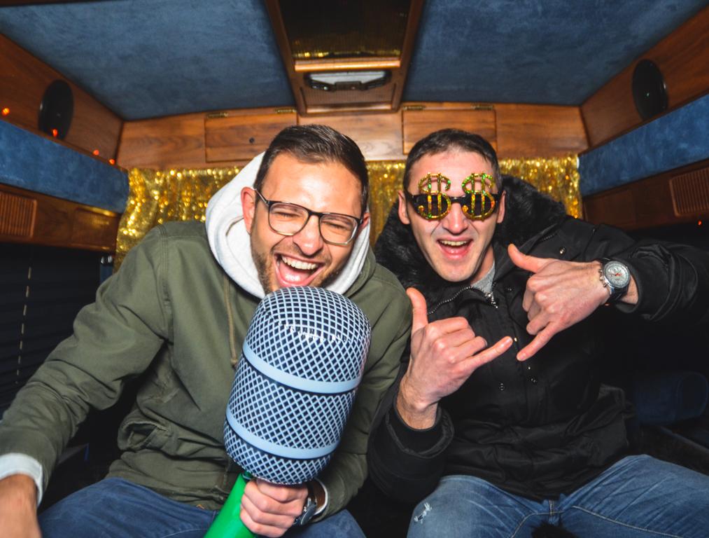 Zwei Männer sind verkleidet mit Brille und Aufblasbarem Mikrofon in einem samtblauen Fotobus.
